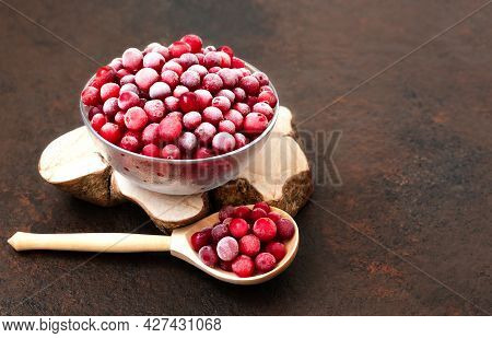 Frozen Cranberries In A Bowl Closeup. Frozen Berries With A Wooden Spoon On A Brown Background. Copy