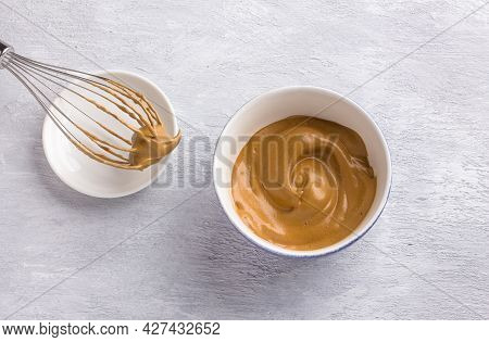 Ceramic Bowl And Whisk With Fluffy Creamy Whipped Coffee Foam On A Light Gray Textured Background. F