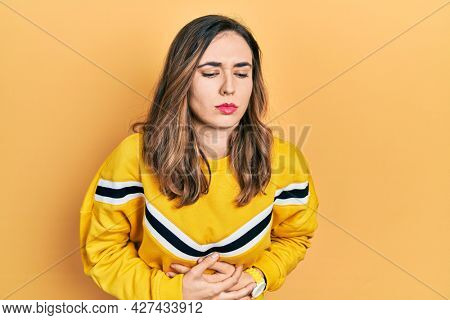 Young hispanic girl wearing casual clothes with hand on stomach because indigestion, painful illness feeling unwell. ache concept.