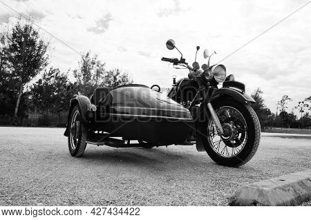 Black And White Image Of Antique, Vintage Motorcycle With Sidecar In Open Lot.