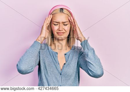 Beautiful blonde woman standing over pink background suffering from headache desperate and stressed because pain and migraine. hands on head.