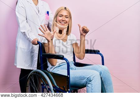 Beautiful blonde woman sitting on wheelchair with collar neck showing and pointing up with fingers number six while smiling confident and happy.