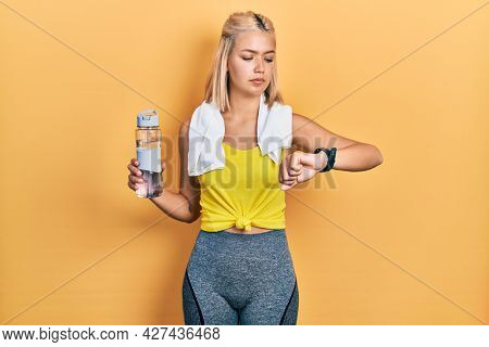 Beautiful blonde sports woman using smart watch relaxed with serious expression on face. simple and natural looking at the camera.