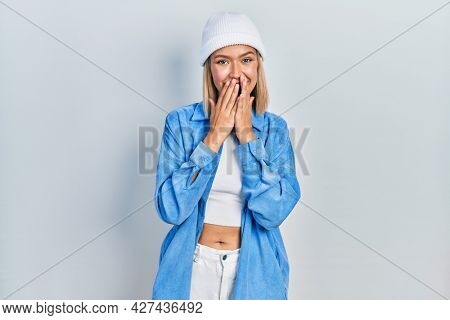 Beautiful blonde woman wearing wool hat laughing and embarrassed giggle covering mouth with hands, gossip and scandal concept