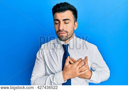 Young hispanic man wearing business clothes smiling with hands on chest with closed eyes and grateful gesture on face. health concept.