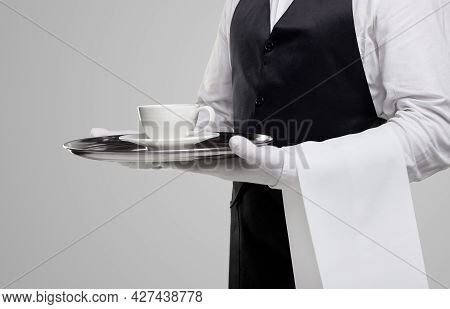 Crop Anonymous Waiter In Elegant Uniform And Gloves Carrying Tray With Cup Of Hot Drink While Servin