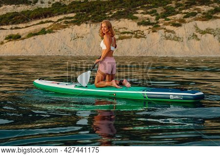 June 25, 2021. Anapa, Russia. Slim Girls On Stand Up Paddle Board At Quiet Sea. Women Sit On Red Pad