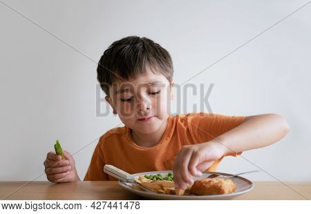 Portrait Of 7-8 Year Old Kid Boy Having Homemade Fish Finger And French Fries For Sunday Dinner At H