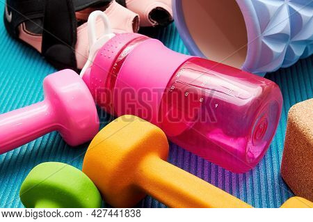 Fitness Equip, Sneakers, Dumbbell, Roller, Bottle, Bricks Lay On The Mat. Sports Equipment And Worko