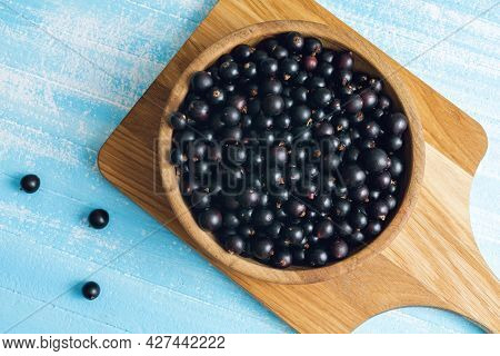 Fresh Black Currant In Wooden Bowl On Blue. Summer Fruit Berry. Healthy Fruits And Food