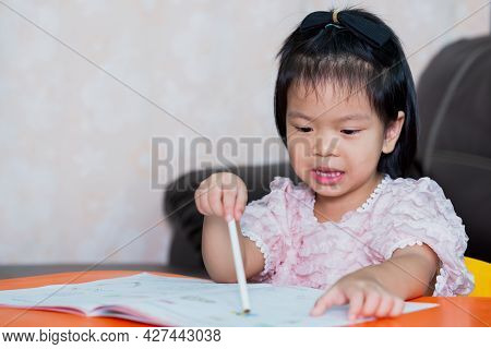 Asian Girl Doing Homework. Cute Child Held A White Pencil And Pointed Suspiciously At Her Book. Kind
