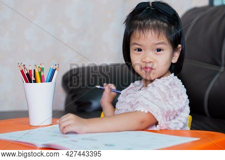 Pretty Asian Girl Learning At Home. Kid Doing Homework. Child Making Cute Face, Wrapping Her Mouth.