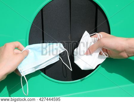 Two Hands Throwing Away Used Surgical Masks After Using Them To Protect Themselves From The Coronavi
