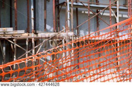 Orange Plastic Net For The Protection Of The Construction Site During The Renovation Of A Building W