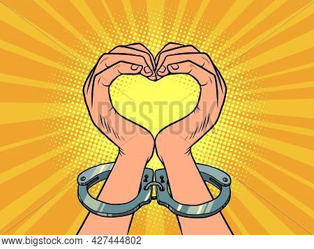 Hands Love Heart Gesture In Handcuffs. A Lover In Prison. A Symbol Of Freedom And Peaceful Protest