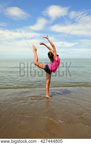 Caucasian Girl Doing Rhythmic Gymnastics Exercises On The Beach In Summer