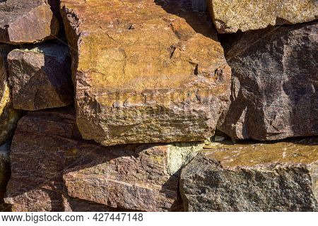 Background Is Made Of Natural Stones Of Different Colors And Sizes. Natural Texture. Brown Granite.