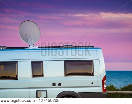 Camper Vehicle Camping On Sea Shore With Satellite Dish On Roof. Tv Connection. Travel Holidays In C