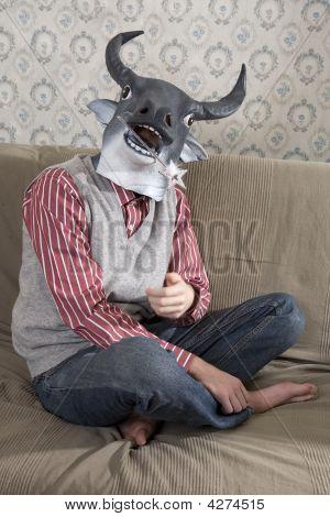 Man wearing mask of bull sitting at the sofa poster