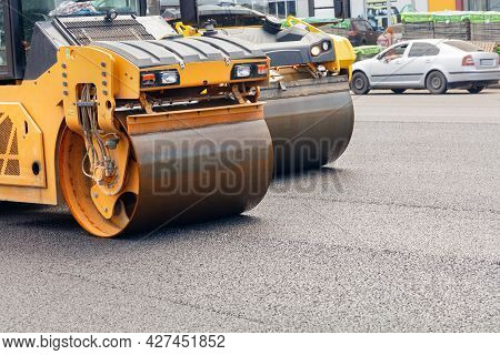 The Metal Cylinders Of Yellow Road Vibratory Rollers Powerfully Compact The Fresh Asphalt On A Road