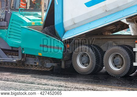 A Dump Truck Unloading Asphalt From Its Body Into An Asphalt Paver At A Construction Site. Close-up,