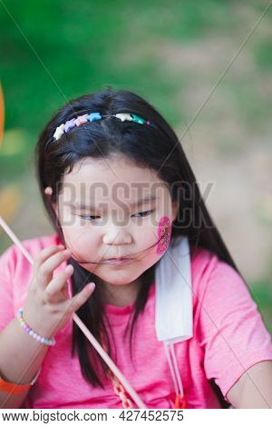 Vertical Image. Asian Girl Sits To Rest From Easter Activities. Children Paint Watercolor Cartoons O