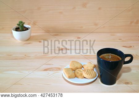 Cup Of Hot Coffee With A Plate Of Biscuits On Wooden Table