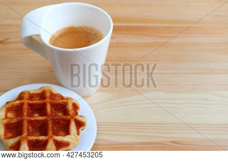 Plate Of A Liege Waffle With Blurry Hot Coffee In Background