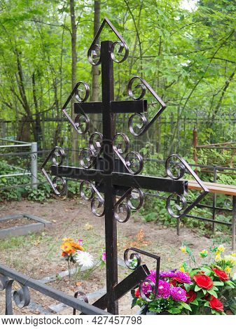 Metal Cross On The Grave. Monument In The Form Of A Cross In The Cemetery. Daytime In Summer. The Th