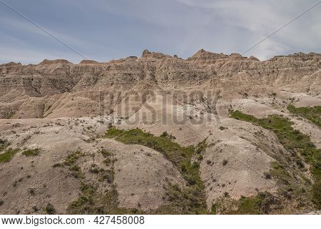Badlands National Park, Sd, Usa - June 1, 2008: Beige-brown Mountain Range With Wide Spread Footing