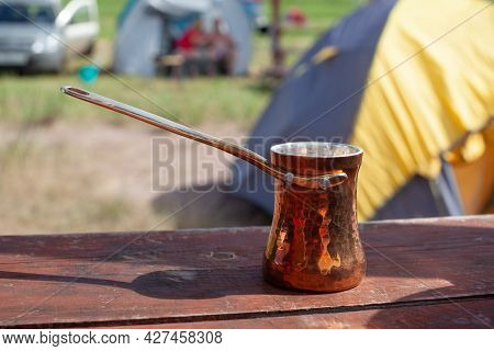 Copper Turkish Coffee Cezve Against Blurred Campsite Background. Making Coffee In Cezve On In Outdoo