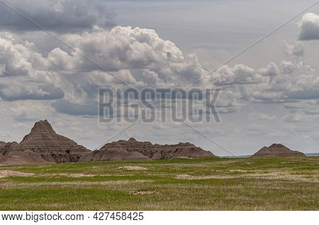 Badlands National Park, Sd, Usa - June 1, 2008: Green And Some Dried Patches Of Plains In Front Of B