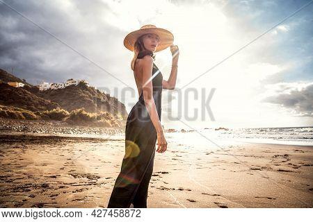 Fashionable Woman On A Sunset Walk On The Beach. Summer Island Vibes.