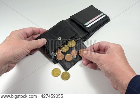 Hands Taking The Few Euro Coins Out Of A Wallet, Money Concept For Poverty And Financial Crisis Duri