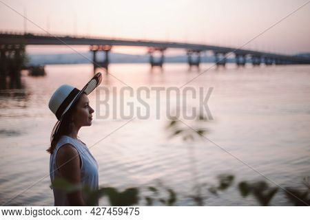 A Woman By The Sea At Sunset. Close-up Portrait In Profile Of A Thoughtful Woman In A Straw Hat Enjo