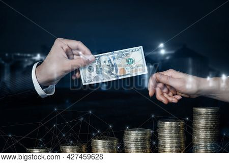 Concept Of Receiving Dividends. Hand Passes Dollars To Another Hand On The Background Of The Growth