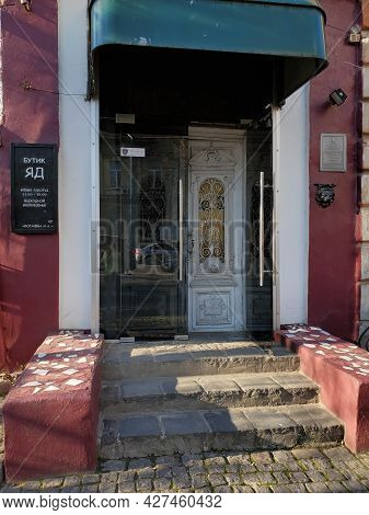 Porch And Front Door Painted In Dark Red Color. Vintage Doorway With Stone Steps Of Building Exterio