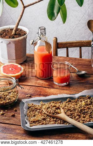Homemade Muesli On Baking Sheet With Wooden Spoon, Grapefruit Juice And Sliced Fruit