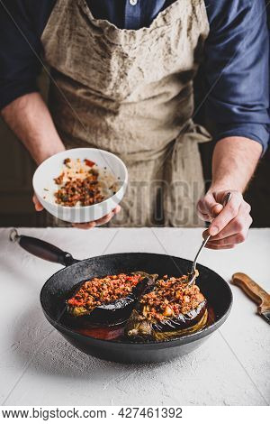 Preparing Eggplants Stuffed With Ground Beef, Tomatoes And Spices. Traditional Dish Karniyarik Of Tu