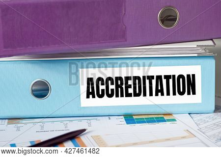 A Lignt Blue Folder With The Label Accreditation.