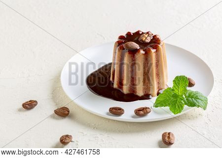 Italian Dessert Panna Cotta With Chocolate Sauce And Decorated With Coffee Beans Is Served On A Whit