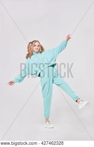 Youth style. Cute teenage girl in trendy mint hoodie and sweatpants poses on a white background. Positive emotions. Full length portrait.