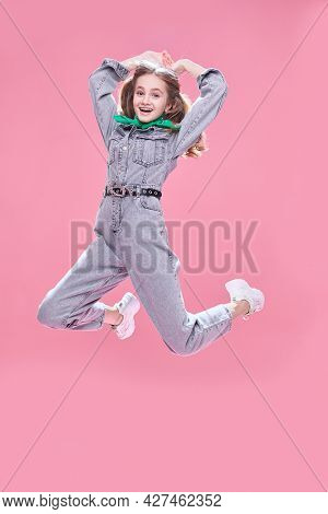 Joyful girl teenager in denim overalls jumping on a pink background. Happiness and active lifestyle. Youth style. Fashion.