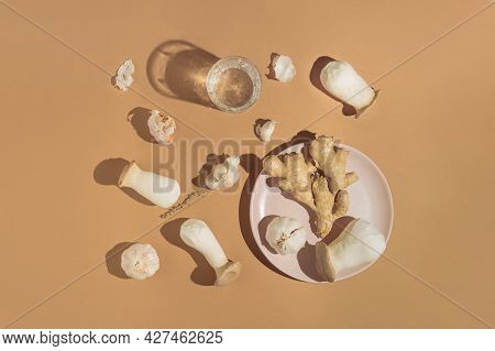 Eringi Mushrooms, Glass Of Water, Garlic And Ginger On A Plate On Pastel Beige Background With Sunli