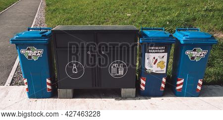 Pavement In Park With Trash Recycling Cans And Lockers For Sorted Garbage. Sustainable Lifestyle In