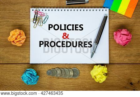 Policies And Procedures Symbol. Words 'policies And Procedures' On White Note. Wooden Table, Colored