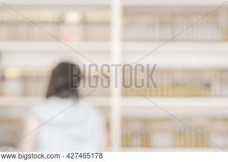 Abstract Blurred Woman In Bookstore, Bookshelves With Books, Library, Book Store. Concept Of Learnin