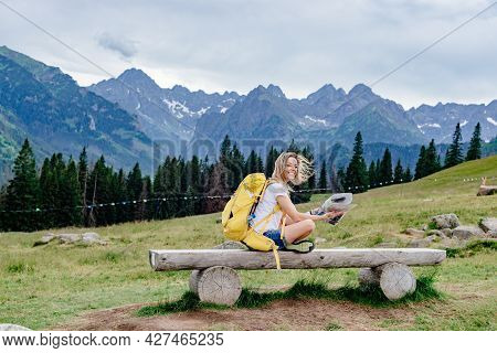 Smiling Girl Traveler With A Yellow Backpack Sits On A Bench With A Paper Map.