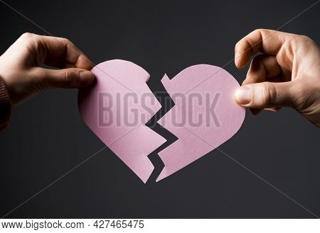 Wo Hands Are Tearing The White Paper Heart. Male And Female Hands Pull The Heart In Different Direct