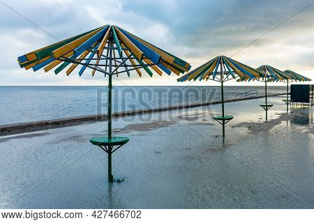 Sea Beach After Heavy Rain, Beach Umbrellas Are In A Puddle. Bad Weather At The Resort.